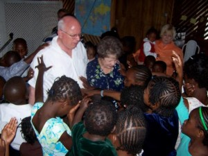 Children at the City of Refuge children's Home in Jamaica pray over former General Superintendent, Thomas Trask and His wife.